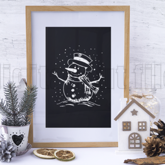 wooden picture frame of snowman on black background with plant and pinecone decorations