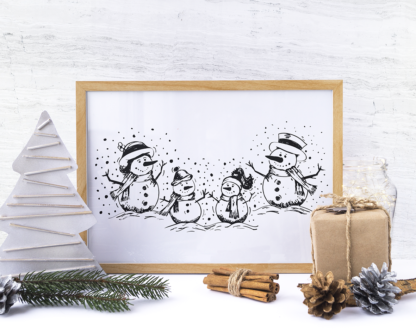 black and white snow family illustration on wood picture frame with festive adornments